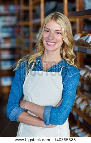 Portrait of smiling female staff standing with hands crossed in supermarket