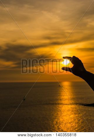 Hands and fingers hold sun at sunset over ocean.