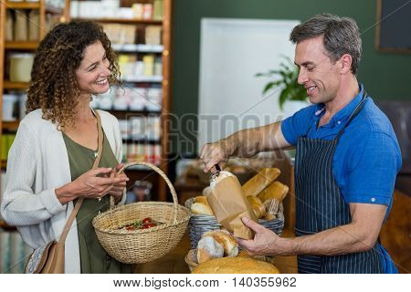 Smiling woman purchasing bread at bakery store in supermarket