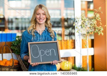 Portrait of smiling female staff holding open sign board in super market