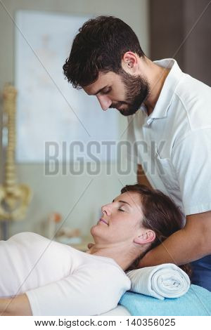 Physiotherapist giving neck massage to a woman in clinic