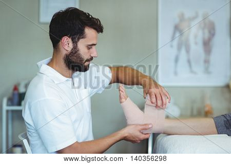 Physiotherapist putting bandage on injured feet of patient in clinic