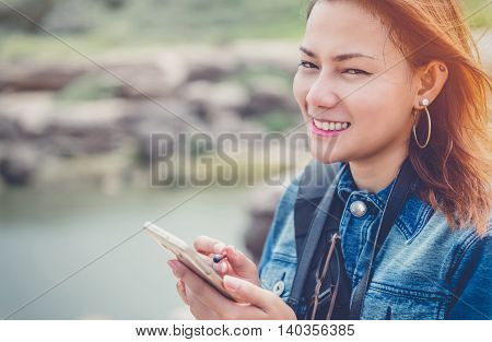 Asia Woman using a cell phone with a smile and good humor.