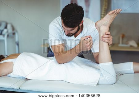 Physiotherapist giving hip massage to a woman in clinic