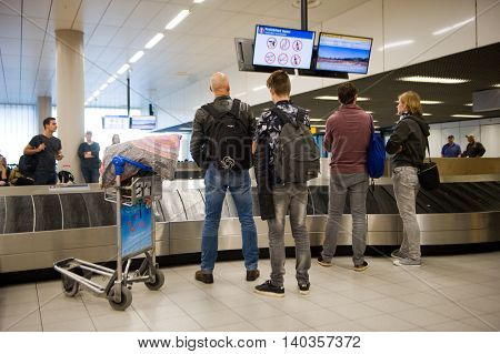 AMSTERDAM THE NETHERLANDS - MAY 05 2016: People are waiting on an airport at the luggage belt for their suitcases to arrive.