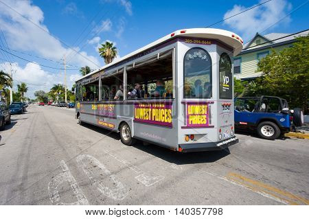 KEY WEST FLORIDA USA - MAY 02 2016: Bus with tourists riding and sightseeing on a street in Key West