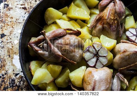 roasted quail with potato wedges and garlic