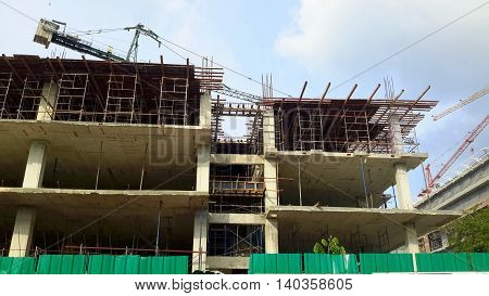 side of three-story building construction site, using concrete and steel, rebar, overhead cranes, wooden scaffolding, Songkhla, Thailand