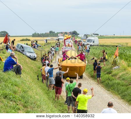 QuievyFrance - July 07 2015: St. Michel Madeleines Caravan during the passing of the Publicity Caravan on a cobblestoned road in the stage 4 of Le Tour de France on July 7 2015 in Quievy France.