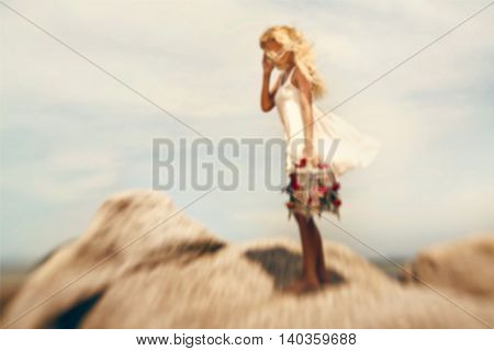 Blurry image of beautiful blonde girl with bird cage on the stone shore. Photo was taken with lens baby