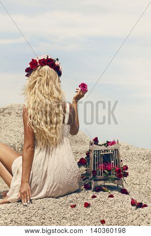 Retro vintage style image of beautiful blonde woman with bird cage full of red roses.