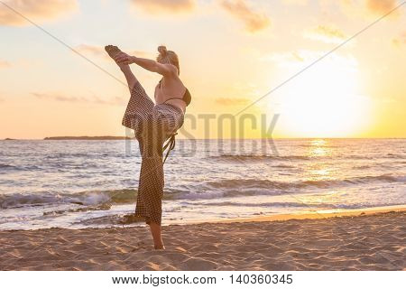 Silhouette of young woman practicing standing bow yoga pose on sandy beach at sunset.