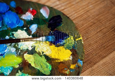 Close up photo of oil paints and brush on palette over wood background. Copy space.