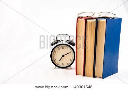 Tree books with alarm clock on white
