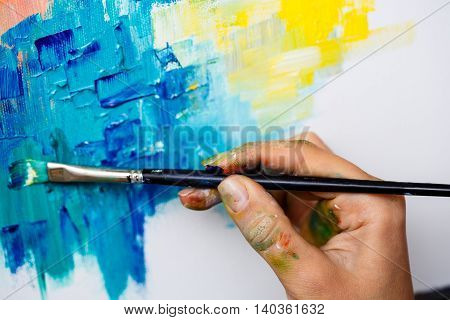 Close up photo of girl drawing with oil paints on canvas. Copy space.
