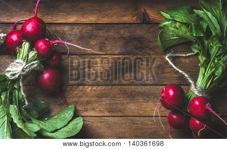 Fresh radish bunches over rustic wooden background, top view, copy space, horizontal composition