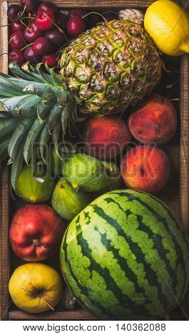 Summer friut variety in wooden tray over wooden background, top view. Watermelon, pineapple, lemon, figs, peach, sweet cherry, apple