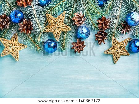New Year or Christmas background: fir branches, blue glass balls, cones and golden stars over blue painted wooden backdrop, top view, copy space