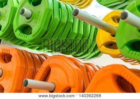 Closeup image of color dumbbells in modern gym
