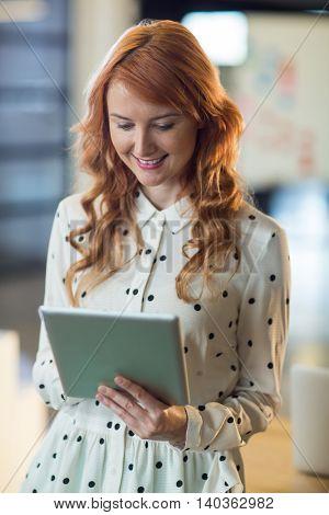 Beautiful woman using digital tablet in office
