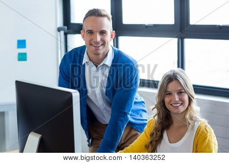 Portrait of smiling young man and woman in creative office