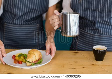 Mid section of two waitresses holding plate of meal and coffee jug to serve in cafe