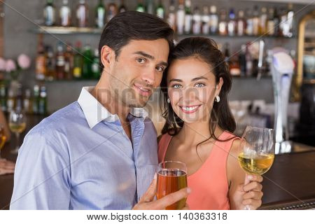 Portrait of romantic couple holding wine glasses in restaurant