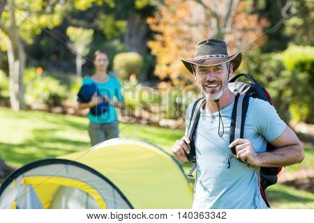 Portrait of hiker standing with rucksack in forest