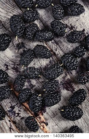 Top view of sweet and fresh organic ripe mulberries on wooden background. Mulberries are scattered on table. Dark style photo.