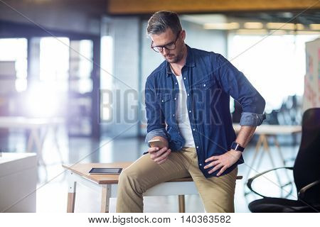 Man using mobile phone while sitting on table in office