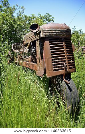 An old one wheeled tractor with a crank is surrounded by long grass