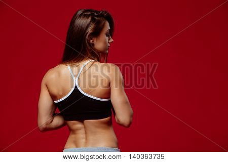 Attractive young woman in sportswear posing on red background. Healthy female model with muscular body in studio.