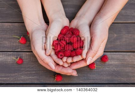 Handful of fresh raspberries in child and mother hands on brown rustic wood background. Harvest, healthy food and parent care concept. Natural ripe organic berries on wooden table, top view.