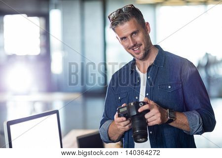 Portrait of man holding camera in creative office