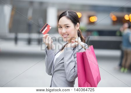 businesswoman take a credit card and bag go shopping in hong kong asian