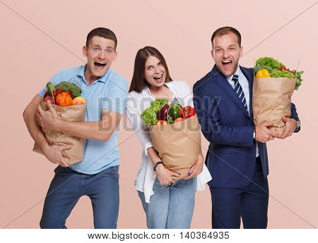 Happy people, two men and young woman hold shopping paper bags full of groceries, vegetables and fruits isolated at pink background. Healthy food shopping, excited buyers