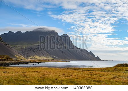 beautiful Icelandic mountain landscape coast yellow field and blue sky in autumn of Iceland