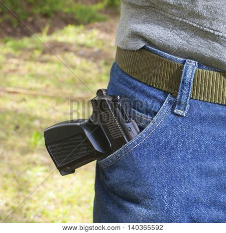 Small handgun hanging out of a pocket on a pair of jeans