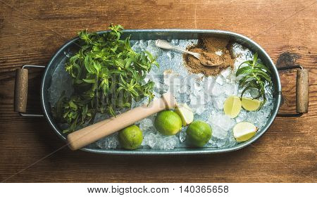 Ingredients for making mojito summer cocktail in metal tray over rustic wooden background, top view