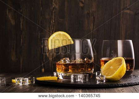 Cognac in glasses over wooden table. Toned image. Space for text. Selective focus