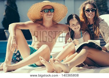 Happy Young Family At Swimming Pool