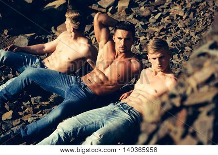 three handsome young macho men with muscular sexy body and six packs on torso in jeans sunny day outdoor on stony natural background