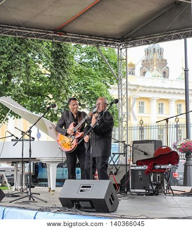 St. Petersburg, Russia - 23 July, Musicians with a guitar and violin at the microphones, 23 July, 2016. Speech by David Goloschekin with his jazz group on the Arts Square in St. Petersburg.
