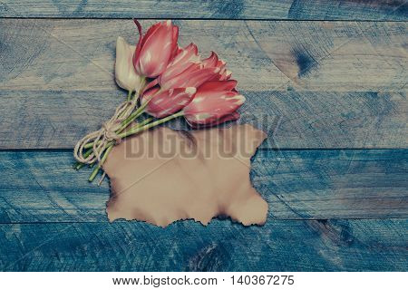 seasonal tulip flower bouquet pink color on green stem in spring with rope and scorched paper on blue wooden background closeup copy space