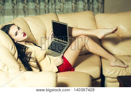 Attractive girl with laptop on the beige couch
