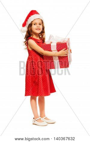 Nice little six years old girl standing with big red box present with white ribbon bow wearing Santa hat