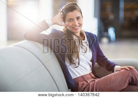 Portrait of smiling young woman sitting on sofa in office