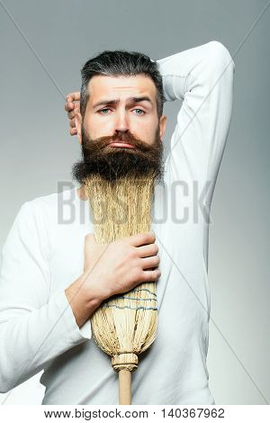 Bearded man with grimace face in white shirt holding broom as beard in studio on grey background