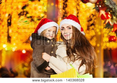 The portrait of mother and her little daughter  and wearing red Santa's hat