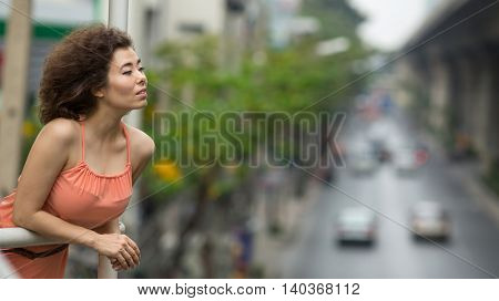 Asian girl portrait in a big city, the background blurred track.